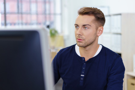 casual office: businessman staring at computer monitor with a serious facial expression Stock Photo
