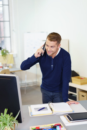 proficient: Businessman standing at his desk taking a call on his mobile phone smiling as her listens to the conversation and checks information on his computer monitor