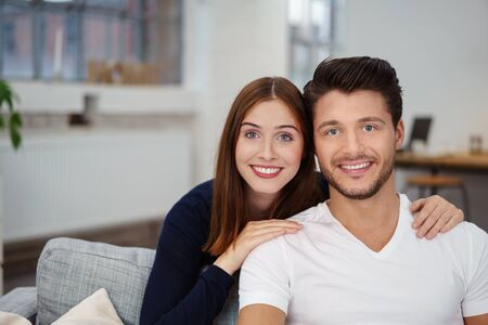 arms around: young couple in love sitting on the sofa with her arms around his shoulders
