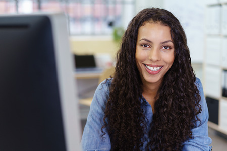 beaming: View past the edge of a desktop computer monitor of an attractive businesswoman with a beaming smile looking at the camera