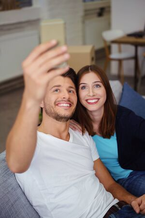 Fun young couple posing for a selfie on their mobile phone as they sit relaxing together on a sofa at home