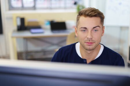 raised eyebrows: young man sitting at a desk in the office working on computer Stock Photo