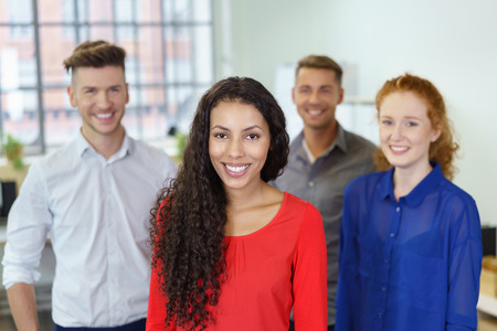 Young Cheerful Office Woman Smiling at the Camera Against Three Colleagues.
