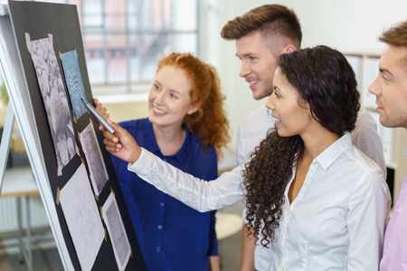 employees: Group of Four Young Office People Brainstorming Using Pictures Pasted on Flip Chart. Stock Photo