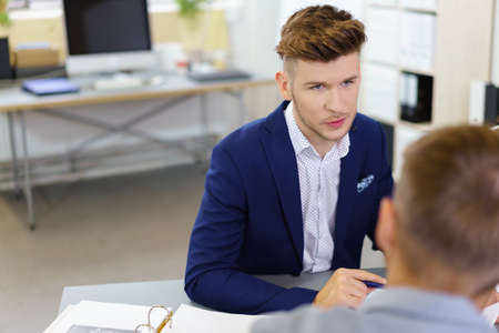 two men: Handsome Young Businessman Talking to his Colleague at his Office Table. Stock Photo