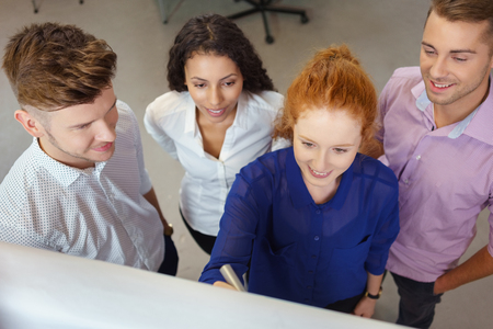 flip chart: High Angle View of Four Young Business People Brainstorming inside the Office Using Flip Chart. Stock Photo