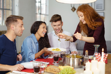 dinner food: Pretty Young Woman Serving Appetizing Food to her Friends Wile Having Dinner. Stock Photo