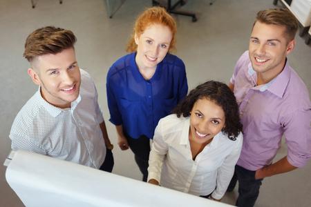 trabajadores: Grupo de cuatro jóvenes trabajadores de oficina feliz sonríe en la cámara Desde el Punto elevada.