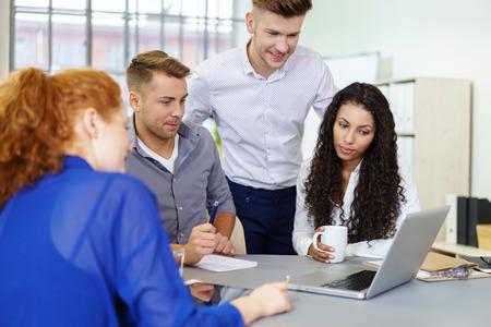 Groupe de quatre jeunes gens d'affaires en regardant quelque chose sur ordinateur portable tout en ayant une réunion à l'intérieur du bureau.