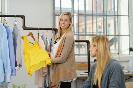 merchandiser: Young Female Fashion Stylist Showing a Trendy Yellow Shirt Design to her Partner Inside the Office. Stock Photo