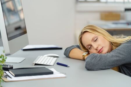 break from work: Tired Young Office Woman Leaning on her Desk with Eyes Closed While Taking Some Rest. Stock Photo