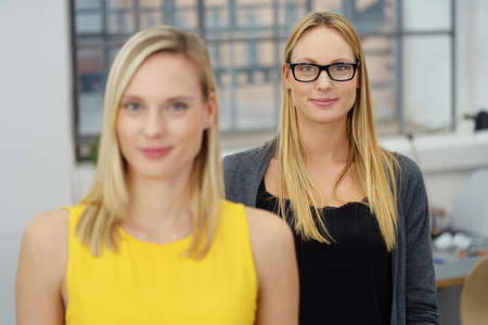 Office women: Half Body Shot of a Young Office Woman Standing Behind her Colleague, Smiling at the Camera. Stock Photo