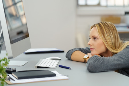 unmotivated: Pensive Young Woman Leaning on her Table and Looking to the Left Inside the Office. Stock Photo
