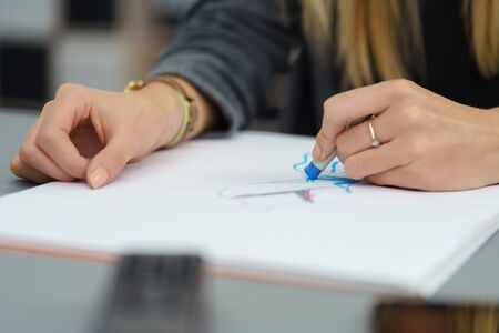 paper art projects: Close up Female Artist Drawing Something on a White Paper at her Desk inside the Office.