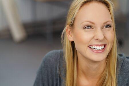 rubia: Cierre de la mujer joven rubia feliz que ríe mientras mira hacia arriba dentro de la oficina.
