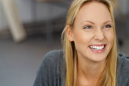 pretty face: Close up Happy Blond Young Woman Laughing While Looking Up Inside the Office. Stock Photo