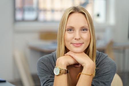 mujer bonita: Cierre de la mujer bastante joven oficina se apoya la barbilla en la mano y sonriendo a la cámara.