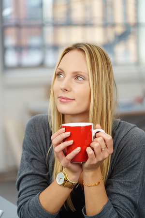 energising: Close up Thoughtful Young Office Woman Holding a Red Cup of Coffee While Looking Up. Stock Photo