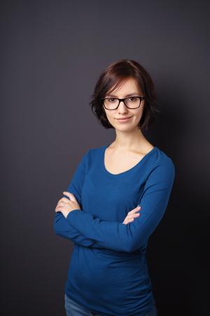 mujer sola: La mitad de tiro del cuerpo de una mujer confidente joven con la sonrisa de las lentes de la c�mara con los brazos sobre el pecho de la traves�a contra el fondo gris de pared