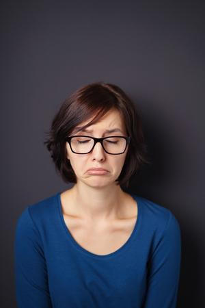 cara triste: Mujer joven con gafas de visión que muestra la cara triste contra la pared gris con copia espacio arriba Foto de archivo