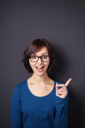 exultant: Half Body Shot of a Shocked Young Woman Looking at the Camera While Pointing her Finger Away Against Gray Wall with Overhead Copy Space.