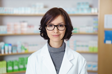eyeglasses: Portrait of a Young Female Pharmacist with Eyeglasses Standing inside a Drugstore and Smiling at the Camera.