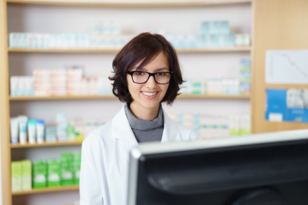 Half Body Shot of a Pretty Young Pharmacist Standing at the Pharmacy Counter and Smiling at the Camera. Archivio Fotografico