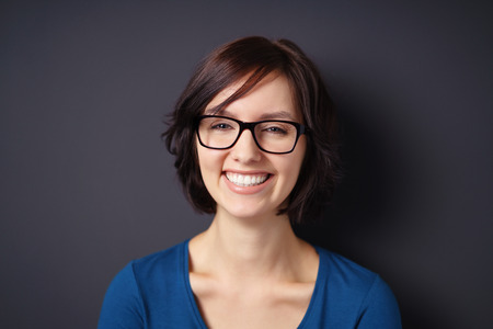people laughing: Close up Happy Young Woman, Wearing Eyeglasses, Showing Toothy Smile at the Camera Against Gray Wall Background. Stock Photo