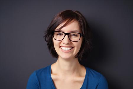 reir: Close up Mujer joven feliz, utilice gafas, mostrando Sonrisa con dientes en la cámara contra el fondo gris de pared.