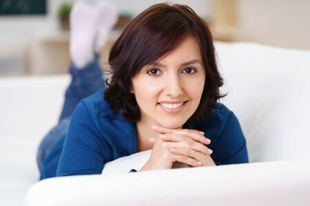 Close up Pretty Young Woman Lying on her Stomach on a White Sofa, Smiling at the Camera Positively. Stock Photo