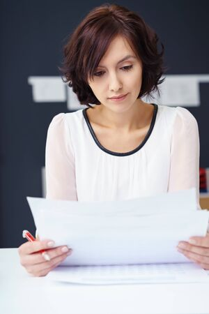 reflect: Close up Young Businesswoman Reading a Business Letter at her Office Table with Serious Facial Expression.