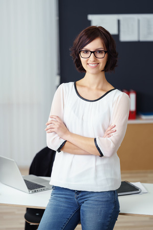 casual office: Three Quarter Shot of a Confident Office Woman Smiling at the Camera with Arms Crossing Over her Chest.