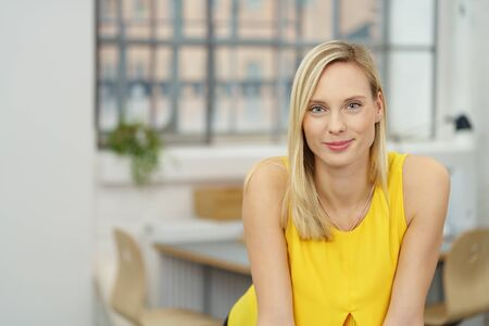 young woman smiling: Half Body Shot of a Pretty Blond Young Office Woman, Smiling at the Camera Positively. Stock Photo