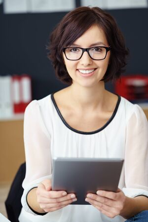 personal assistant: Close up Happy Office Woman, Wearing Eyeglasses, Holding a Tablet Computer and Smiling at the Camera.