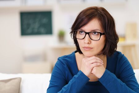 chin on hands: Thoughtful Adult Woman Wearing Eyeglasses, Sitting at the Living Room and Looking Up With Chin Resting on Hands