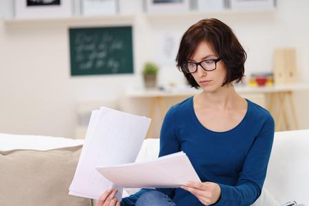 Jonge vrouw lezen van een aantal documenten Serieus tijdens de vergadering op de bank in de woonkamer. Stockfoto - 48654571