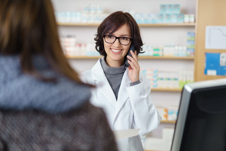Happy Female Pharmacist Talking to Someone on Phone to Verify Something In Front of a Customer Inside a Drugstore.