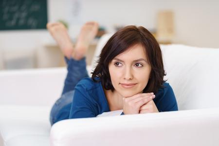 Продуманный молодая женщина, лежа на диване в гостиной, склонив симпатичное лицо на ее руки и глядя в сторону.