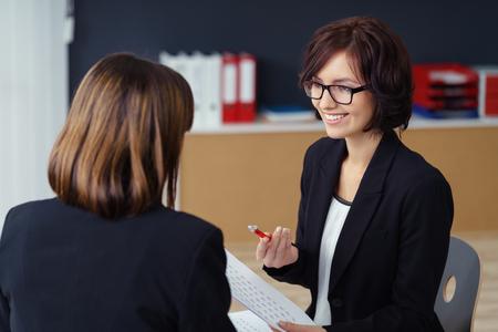 patron: Alegre Administrador Mujer Hablando con su subordinado en su mesa dentro de la oficina.