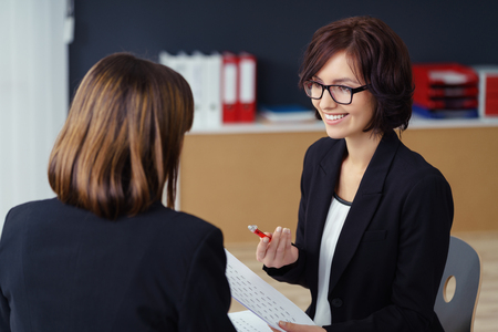 lady boss: Cheerful Female Manager Talking to her Subordinate at her Table Inside the Office.