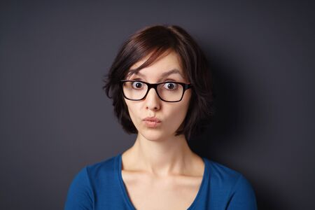 sceptical: Close up Young Woman with Eyeglasses Looking at the Camera with Shocked Facial Expression Against Gray Wall Background.