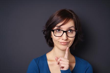 dedo indice: Cierre de Pensativo mujer joven con su dedo índice en la cara contra la pared del fondo gris.