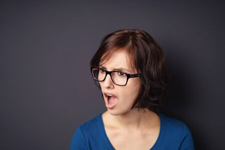appalled: head and Shoulder Shot of a Disgusted Woman with Eyeglasses, Looking Away with Mouth Open Against Gray Wall with Copy Space.