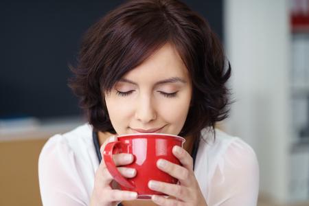 가 까이 서 그녀의 커피의 아로마를 냄새 맡는 꽤 젊은 오피스 여자 눈을 가진 빨간 컵에서 마신다.