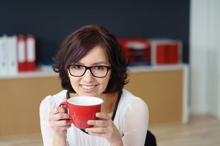 drink coffee: Happy Young Office Woman Holding a Red Cup of Coffee and Smiling at the Camera Positively. Stock Photo