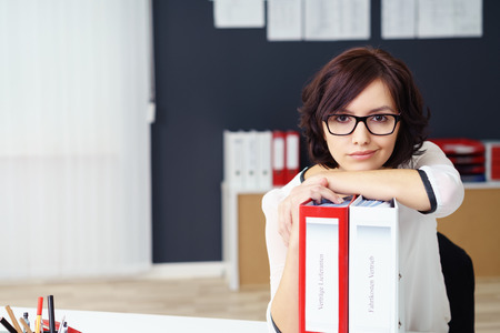 wry: Young Office Woman Leaning on File Binders on the Top of her Table and Looking at the Camera with Half Smile Face.