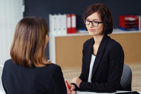 personas escuchando: Bastante empresaria joven que escucha a su colega de hablar con ella en su mesa dentro de la Oficina. Foto de archivo