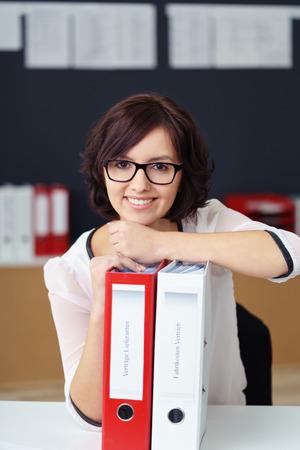 secretaria: Retrato de una mujer de oficina con Encanto Apoyado en carpetas de archivos en la parte superior de la mesa y mirando a la cámara con expresión facial feliz.