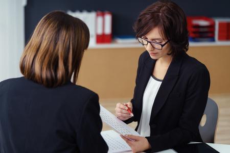 mujeres sentadas: Dos empresarias profesionales con trajes negros tienen una reunión de uno-a-uno de negocios dentro de la oficina.