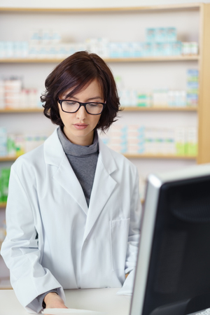 half body: Half Body Shot of a Young Female Pharmacist at the Pharmacy Counter Busy Checking of Something. Stock Photo